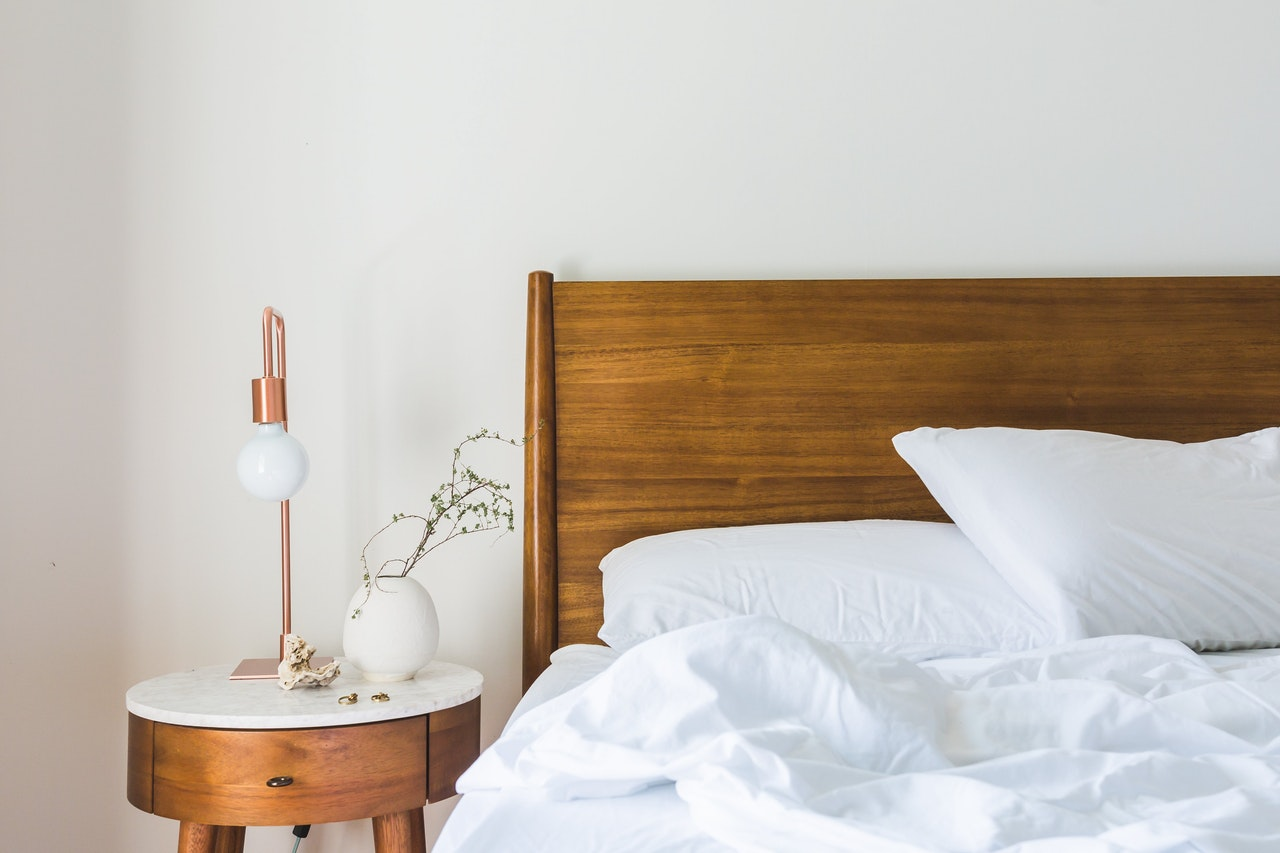a night table next to the bed with white bedding and a wooden headrest
