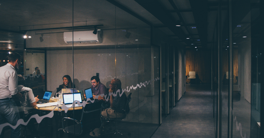 group of people in the conference room, behind glass partition