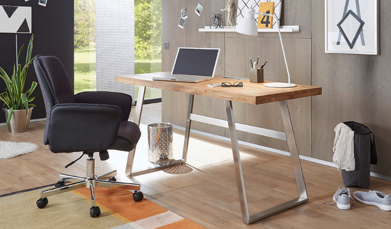 wooden oak desk and a black office chair in a home office