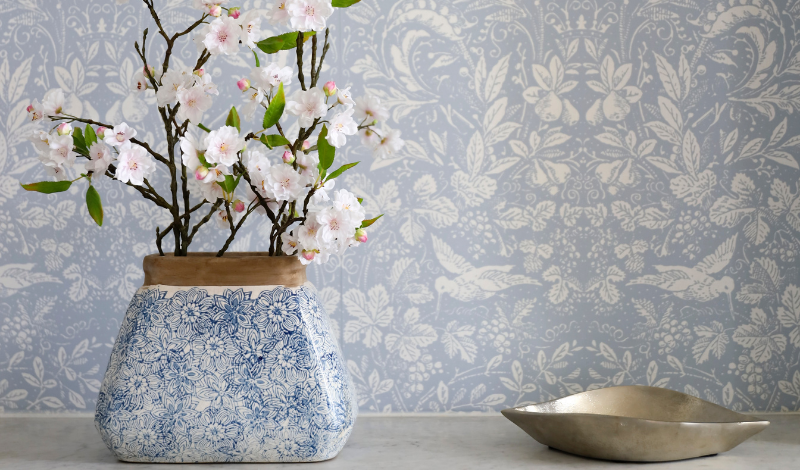 Blue vase with flowers on a background of patterned wallpaper