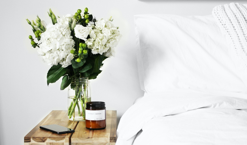 close-up on white bedding and white flowers set in a vase on the bedside table