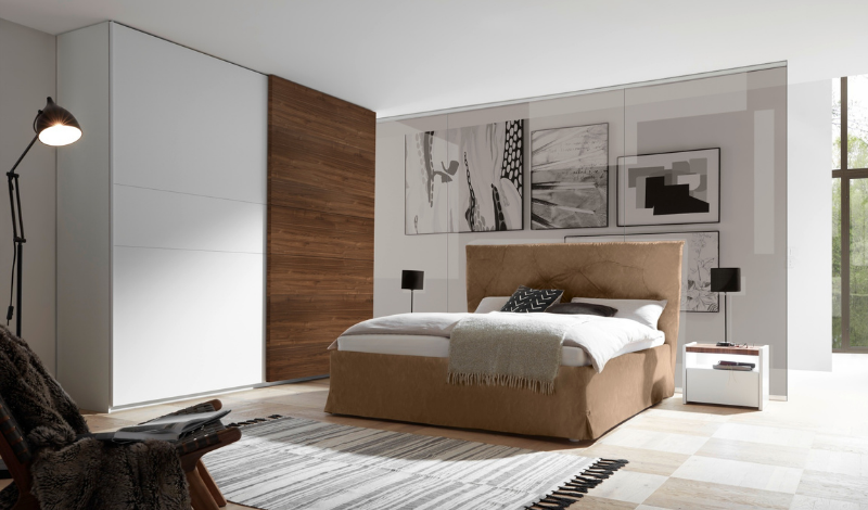 brown double bed in the bedroom with light-coloured bedding
