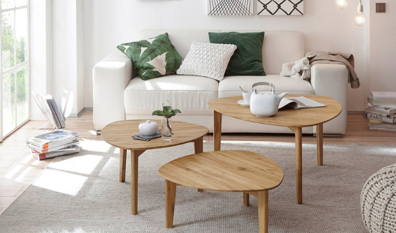 three wooden coffee tables in the living room in front of the white sofa