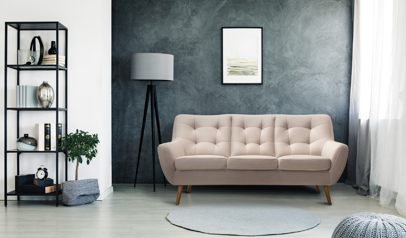 A simple minimalist three-seater sofa, next to it a standing lamp with a white shade on the background of a dark grey wall