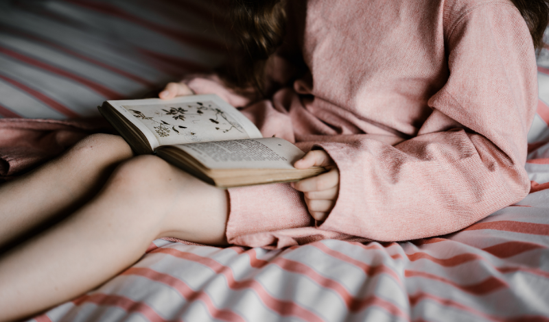 A girl in a pink dress holding a book