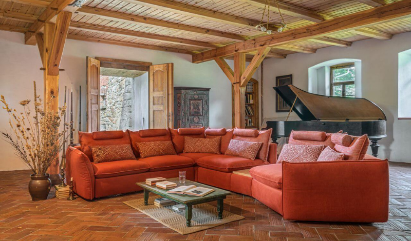 a big l-shaped orange sofa in a living room with wooden beams on the ceiling