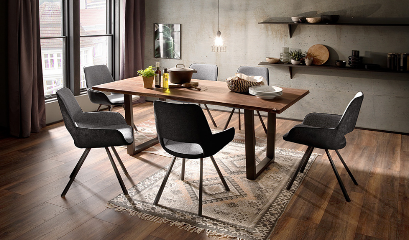 wooden dining table and dining chairs upholstered in dark grey fabric