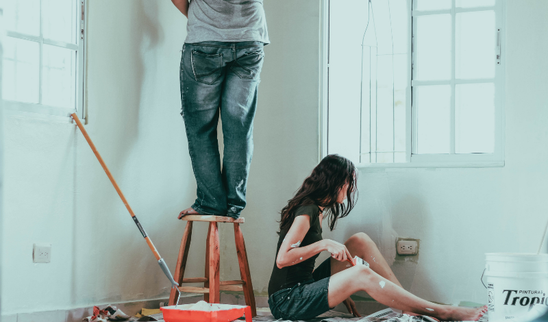 a couple painting a new interior