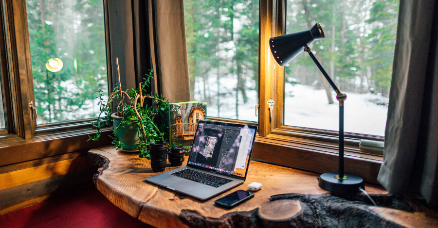 a raw wooden desk with a MacBook on it
