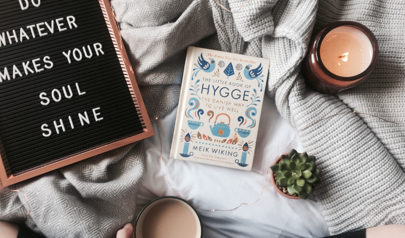 a book on Hygge, a candle, a mug of cocoa and a plaque with the inscription on the bedding