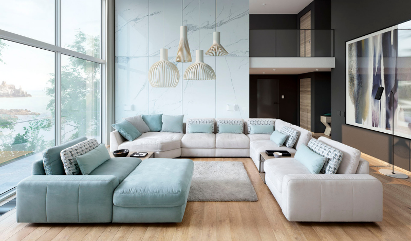 a blue and white big corner sofa with light-blue pillows in a cosy living room