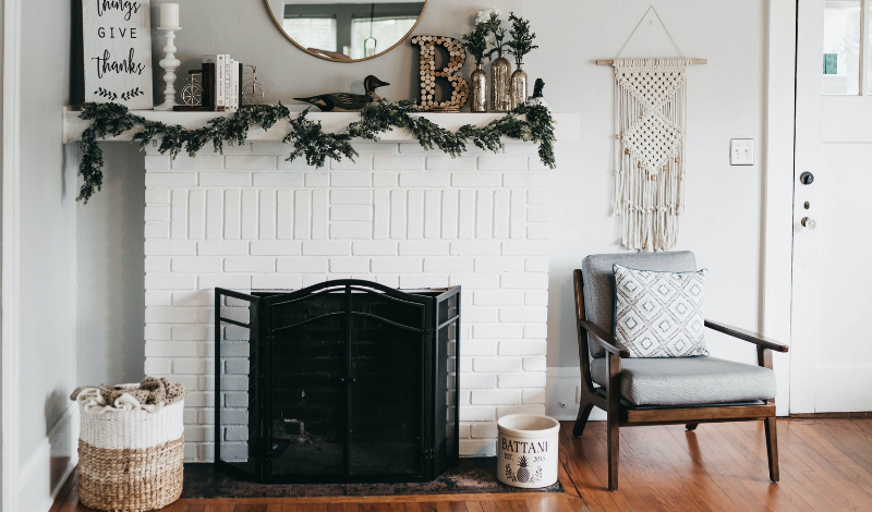 a white stone fireplace with an armchair beside