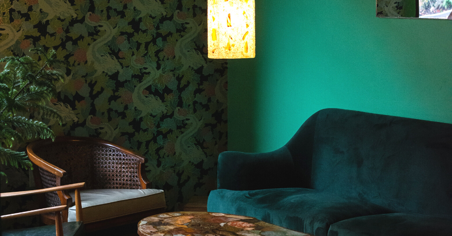 a dark green living space with velvet green sofa and a patterned wallpaper