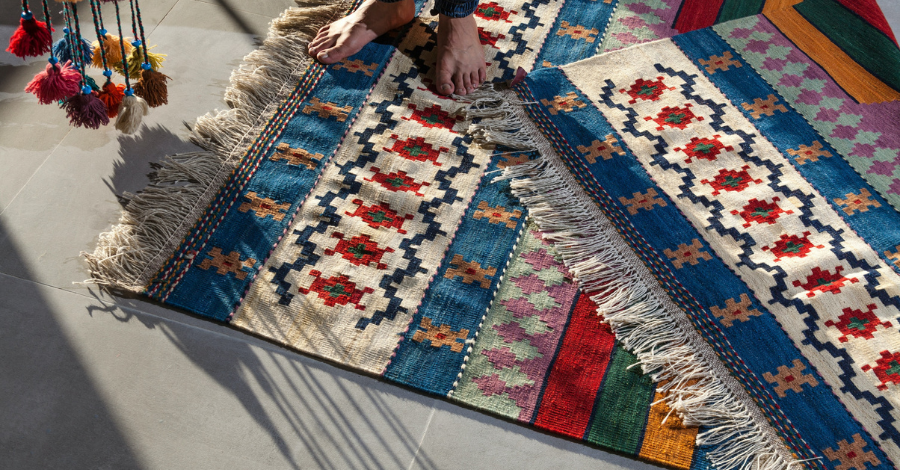 two colorful rugs and bare feet standing on them