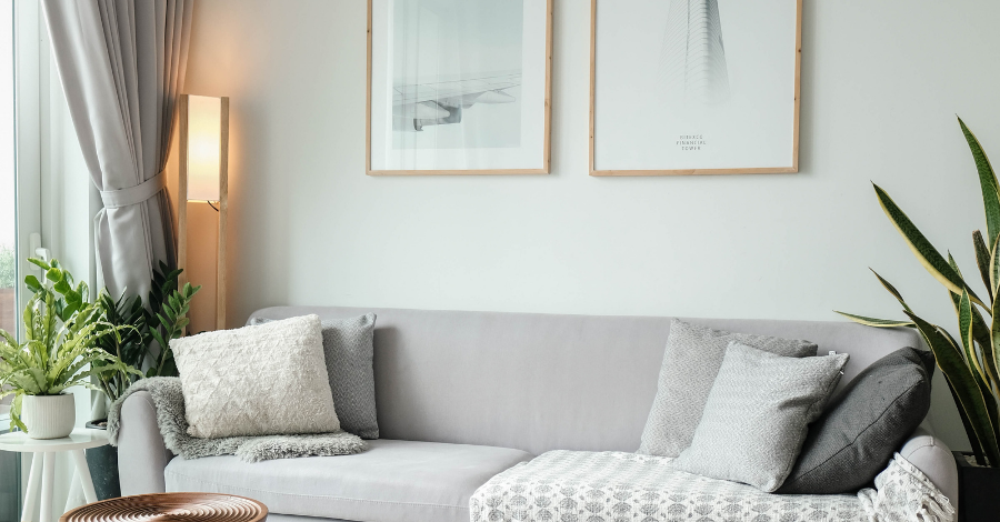light grey sofa by the wall with two delicate paintings