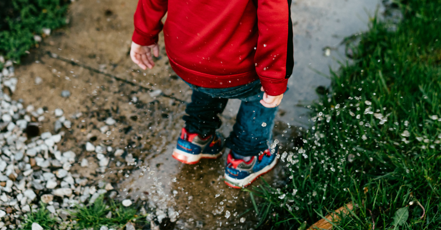 a young child in a red jacket jumping into the puddle