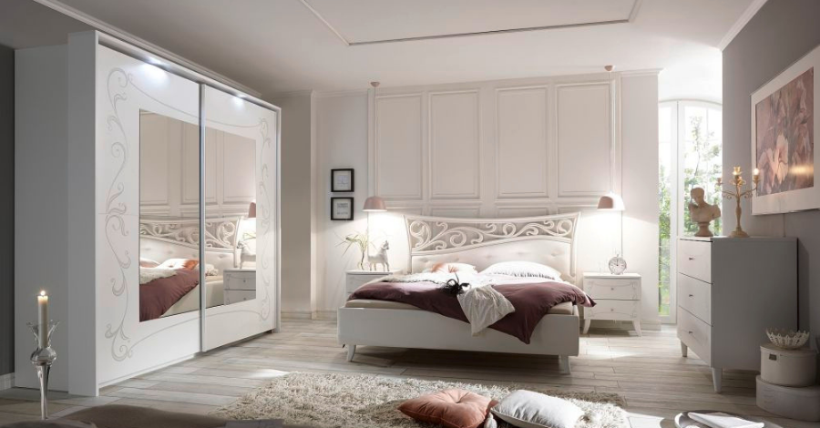 a white bedroom with a bed and a mirrored wardrobe
