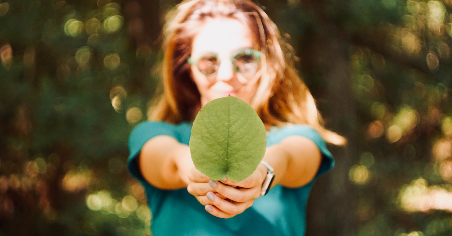 a woman with a green leaf in hands