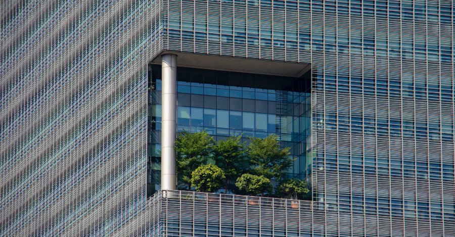 a balcony in a skyscraper with a lot of green trees