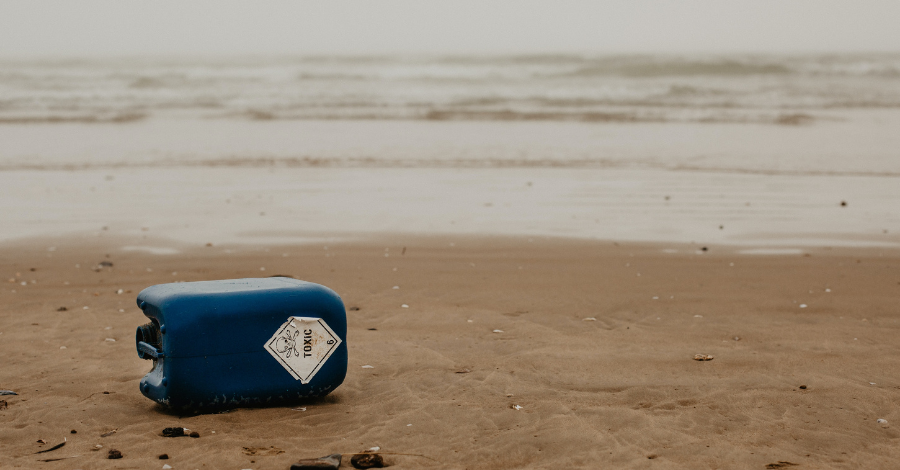 a blue container with toxic label left on the beach