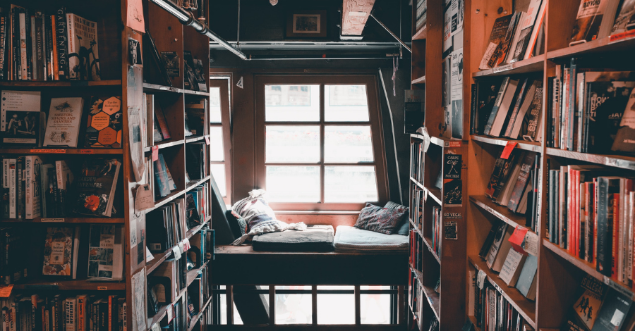 a reading nook with a lot of books and a window